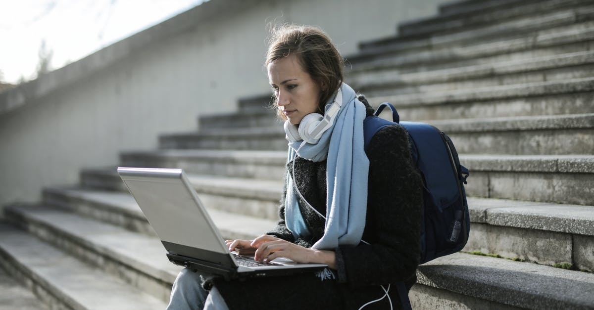 A person using a laptop computer sitting on top of a bench